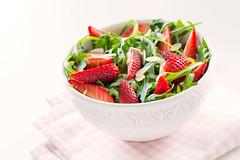 Healthy salad featuring arugula, fresh strawberrie…