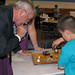 An Española student explains a circuit board to a Science Showdown visitor.