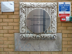 "A round brushed-metal plaque in a square moulded-concrete frame set into a brick wall.  A fire alarm button and a door release switch are to the right.  The plaque reads: ""CVA Resource Centre / Opened on 29 July 2009 by Cllr Steve O'Connell (Croydon Cabinet Member for Regeneration and Economic Development and Assembly Member for Croydon and Sutton) and Mrs Angela Bothwell (one of the founders of Volunteer Centre Croydon)""."