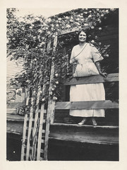 Woman stands next to a flowered-covered porch lattice 2