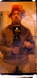 reflected self-portrait with Folding Ensign 3¼ camera and yellow hat