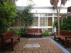 A small outdoor space with three sturdy brown benches arranged as three sides of a square around a paved area with a mosaic tile order.  Trees and plants are around, light comes from above, and a hospital corridor is visible through windows in the background.