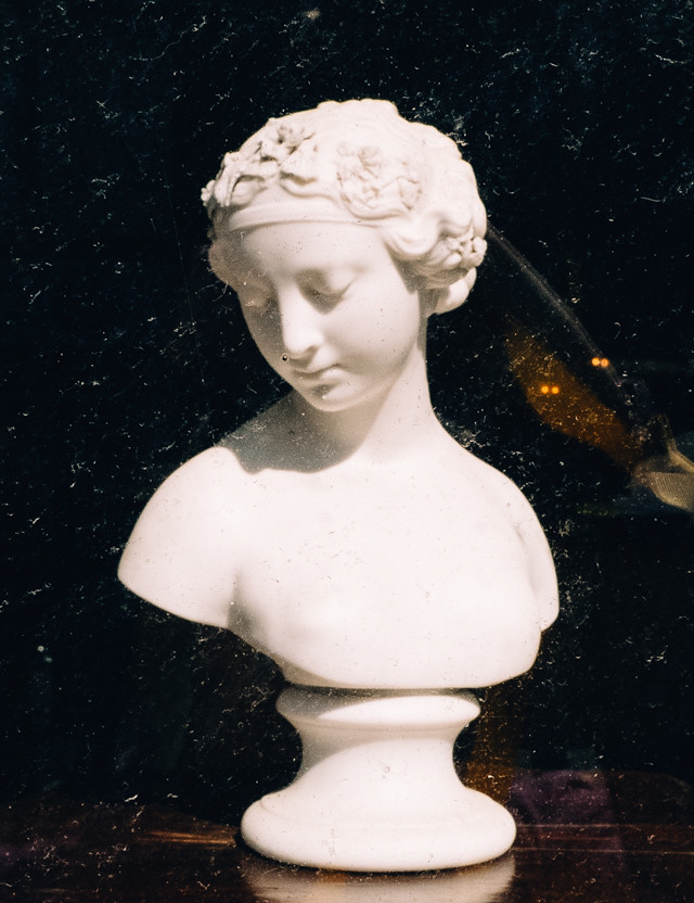 bust in window of antique shop