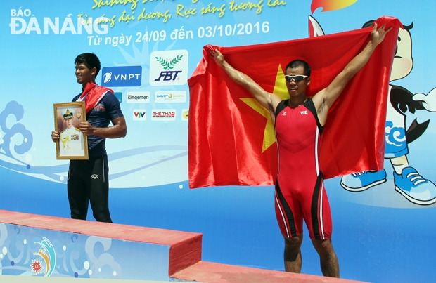 Thay vì cầm là cờ của Tổ quốc khi lên bục nhận huy chương, nam VĐV ở môn Rowing của Thái Lan (trái) luôn mang theo tấm hình thần tượng của mình.