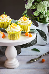Cupcakes with cream cheese on white support.