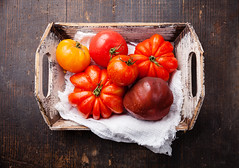 Ripe fresh colorful tomatoes in wooden box on dark…