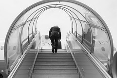 U.S. Secretary of State John Kerry - seen in black-and-white - climbs the stairs to his airplane for a flight to Geneva, Switzerland, after leading a delegation representing President Obama as Muhammadu Buhari replaced Goodluck Jonathan at President of Nigeria during an inauguration ceremony in Abuja, Nigerian, on May 29, 2015. [State Department photo/ Public Domain]