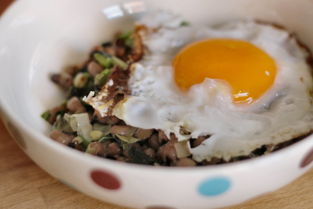 Leek, beans and an egg in a bowl