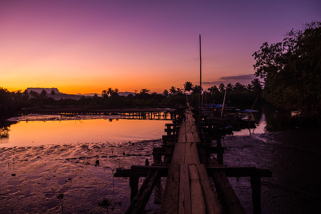 Brilliant purple and orange sunset over Bahia de Miel River wth bridge in Baracoa, cuba.jpg