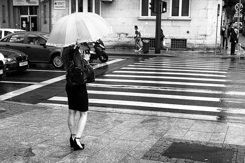 street streets streetphotography city urban cluj clujnapoca romania blackwhite blackandwhite black white monochrome canon 6d woman alone rain umbrella crosswalk green light waiting lensbaby twist 60