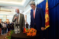 U.S. Charge d'Affaires Andrew Mann presents U.S. Secretary of State John Kerry with toys for his grandchildren before the Secretary addressed employees and family members from U.S. Embassy Sri Lanka on May 3, 2015, in Colombo, Sri Lanka. [State Department Photo/Public Domain]