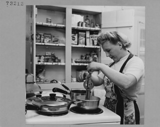 Scottish immigrant Mrs. T. Laing preparing dinner in her kitchen, Ottawa / Madame T. Laing, immigrante écossaise, prépare le souper dans sa cuisine, à Ottawa