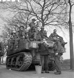 "Personnel of the Royal Hamilton Light Infantry aboard a Sherman tank of ""B"" Squadron of the Fort Garry Horse... / Membres de l'infanterie légère Royal Hamilton sur un char d'assaut Sherman de l'escadron B du régiment Fort Garry Horse..."