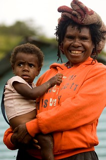 An indigenous Papuan woman and her child are standing in front of puskesmas