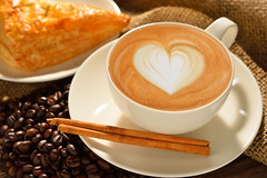 A cup of cafe latte with coffee beans and puff pas…