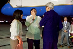 Filipino Department of Foreign Affairs Chief of Protocol Jerril Santos laughs after U.S. Secretary of State John Kerry remarked about a traditional lei presented to him on July 26, 2016, at Villamor Airport in Manila, Philippines, after he arrived for a visit that will include meetings with newly elected President Rodrigo Duterte and Foreign Secretary Perfecto Yasay. [State Department Photo/ Public Domain]
