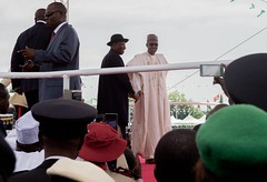 Former Nigerian President Goodluck Jonathan, in hat, stands with newly sworn-in President Muhammadu Buhari amid his inauguration ceremony - attended by U.S. Secretary of State John Kerry and other members of a delegation representing President Obama - at Eagle Square in Abuja, Nigeria, on May 29, 2015. [State Department photo/ Public Domain]
