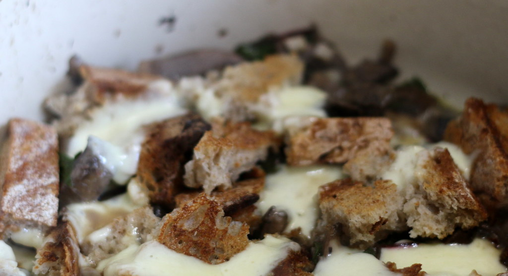 Greens and mushrooms with toast in caserole