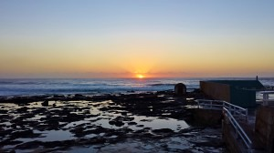 Sunrise on the coast.  To the right is the man made salt water pool