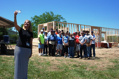 Homeowner Michelle Amrine taking a selfie with a crew of folks helping her build her home