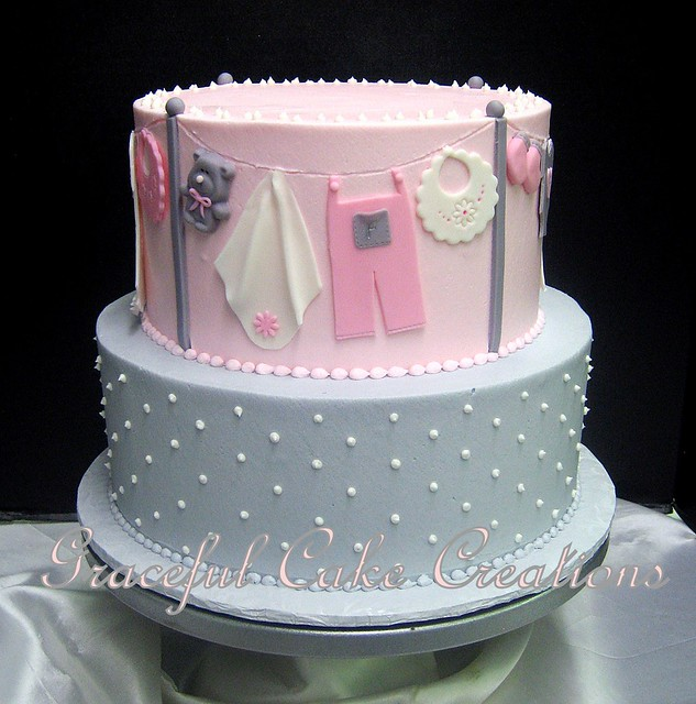 pink and grey baby shower cake with swiss dots and baby clothes