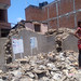 Girl standing amid rubble in village on way to Sindupolchowk