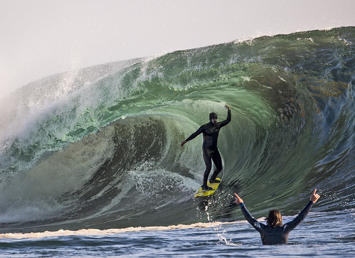 Man riding wave and another man in the water