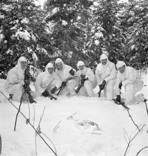 Infantrymen of the Régiment de la Chaudière, who are wearing British winter camouflage clothing, on patrol... / Soldats d'infanterie du Régiment de la Chaudière en patrouille hivernale, vêtus d'habits de camouflage de conception britannique...